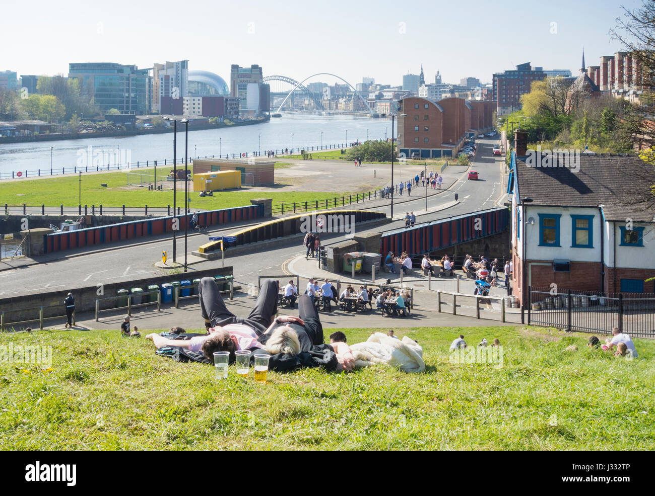 """Newcastle Quayside: View down river Tyne from grassy bank near """"Tyne Bar"""" pub at Ouseburn. Newcastle upon Tyne. Stock Photo"""