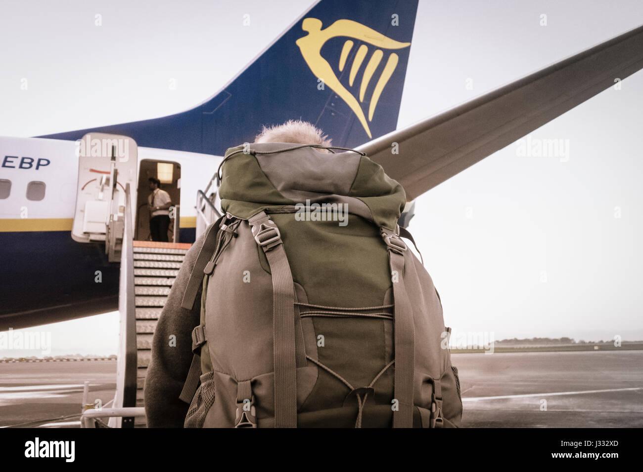 Backpacker boarding Ryanair flight. - Stock Image