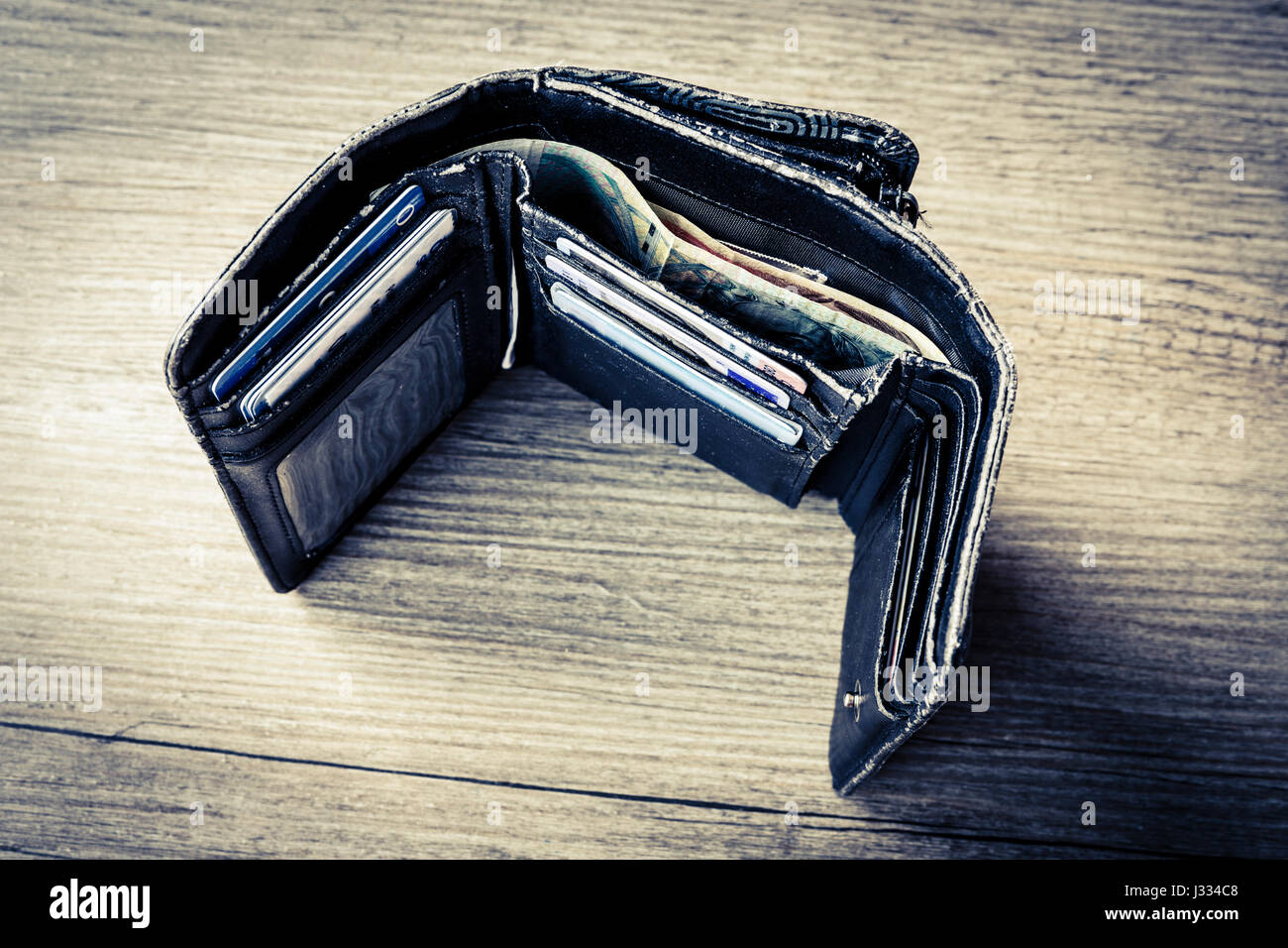 open black woman wallet with money and id cards on the wooden table - Stock Image