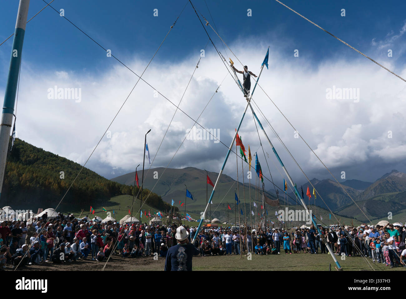 An Uzbek tightrope performer walks above the crowd at Kyrchyn Gorge at last week's World Nomad Games in Kyrgyzstan. - Stock Image