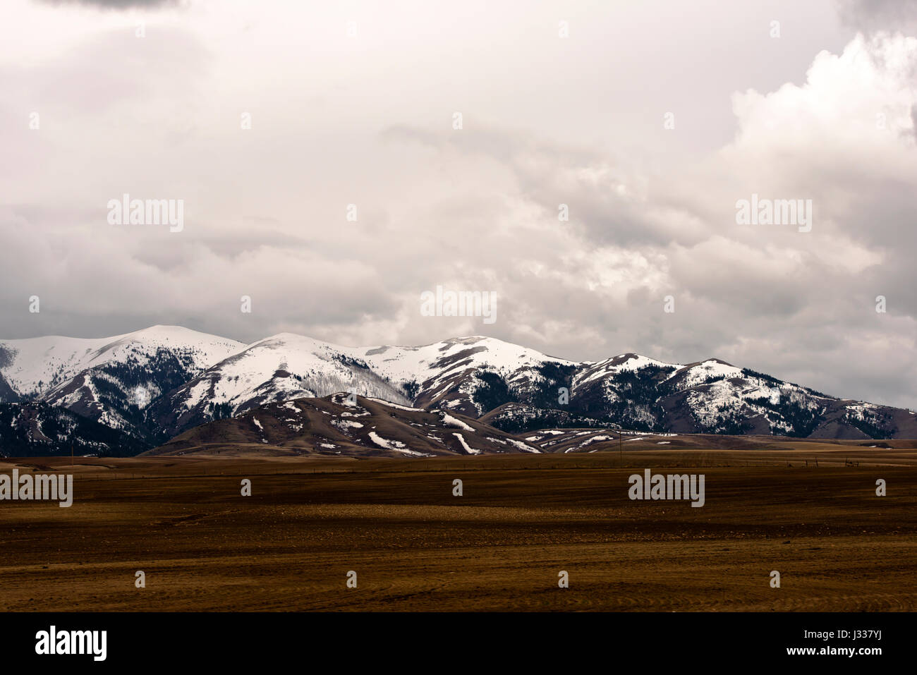 Number of snow-covered mountains on a background of brown fields and gray cloudy sky in Utah - Stock Image