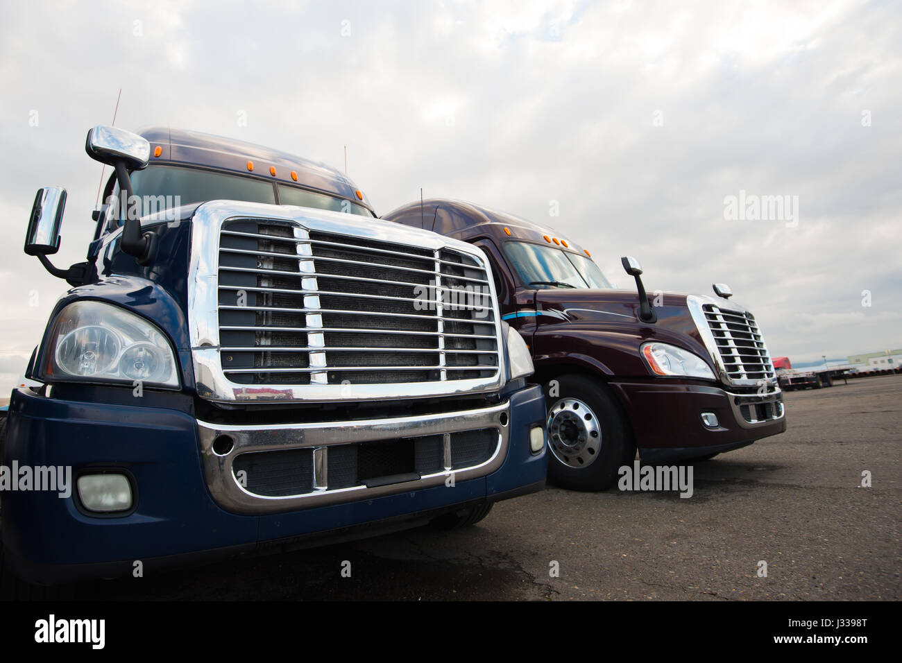 Grilles and headlights of modern semi trucks like the eyes and mouth of huge monsters, bristling gloss chrome lined - Stock Image
