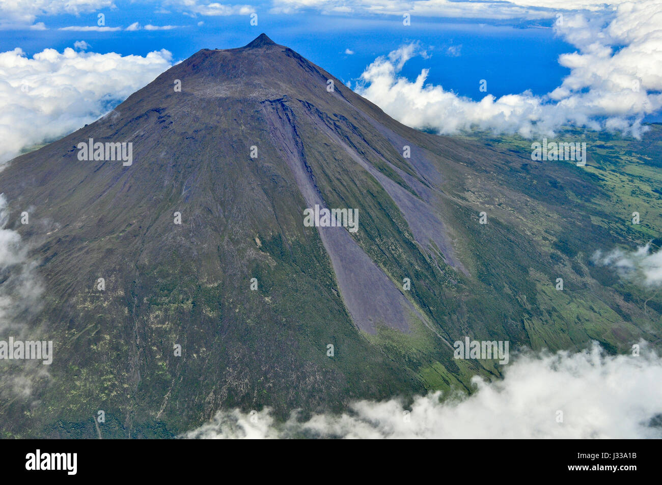 Aerial of volcano Montanha do Pico, Mount Pico with summit Pico Pequeno and crater above clouds, highest mountain - Stock Image