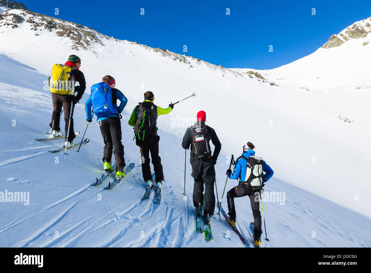 Mountain Guide ski touring with a group, avalanche assessment on a ski tour, risk management with groups, Heidelberger Stock Photo