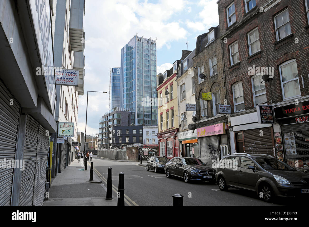 View of old 19th C terraced shops on White Church Lane with view of modern tower block at Goodman's Fields Stepney - Stock Image