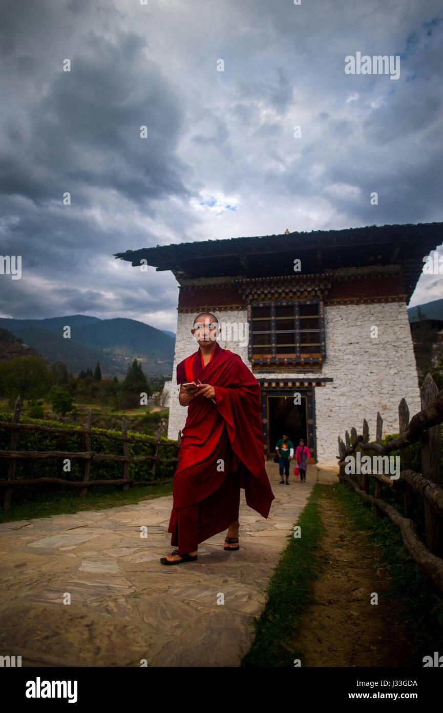 Buddhist monk coming out of the gate of famoush Punakha Dzong Monastery in Punakaha, Bhutan - Stock Image