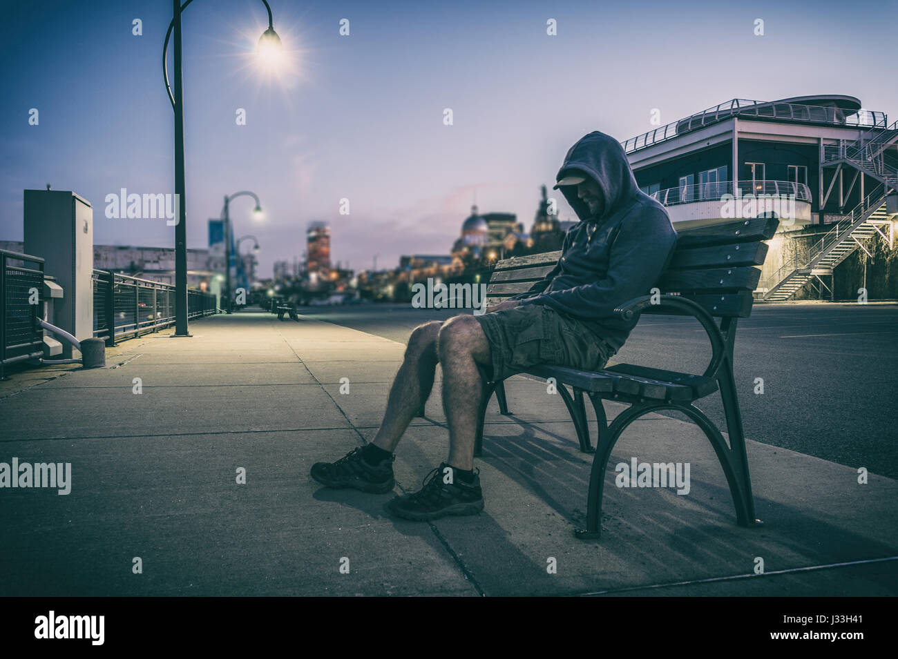 Sad and lonely man with hidden face sitting on a bench at sunset - Stock Image
