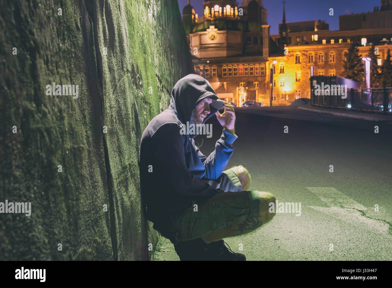 Sad and lonely man with hoodie sitting against a wall at night - Stock Image