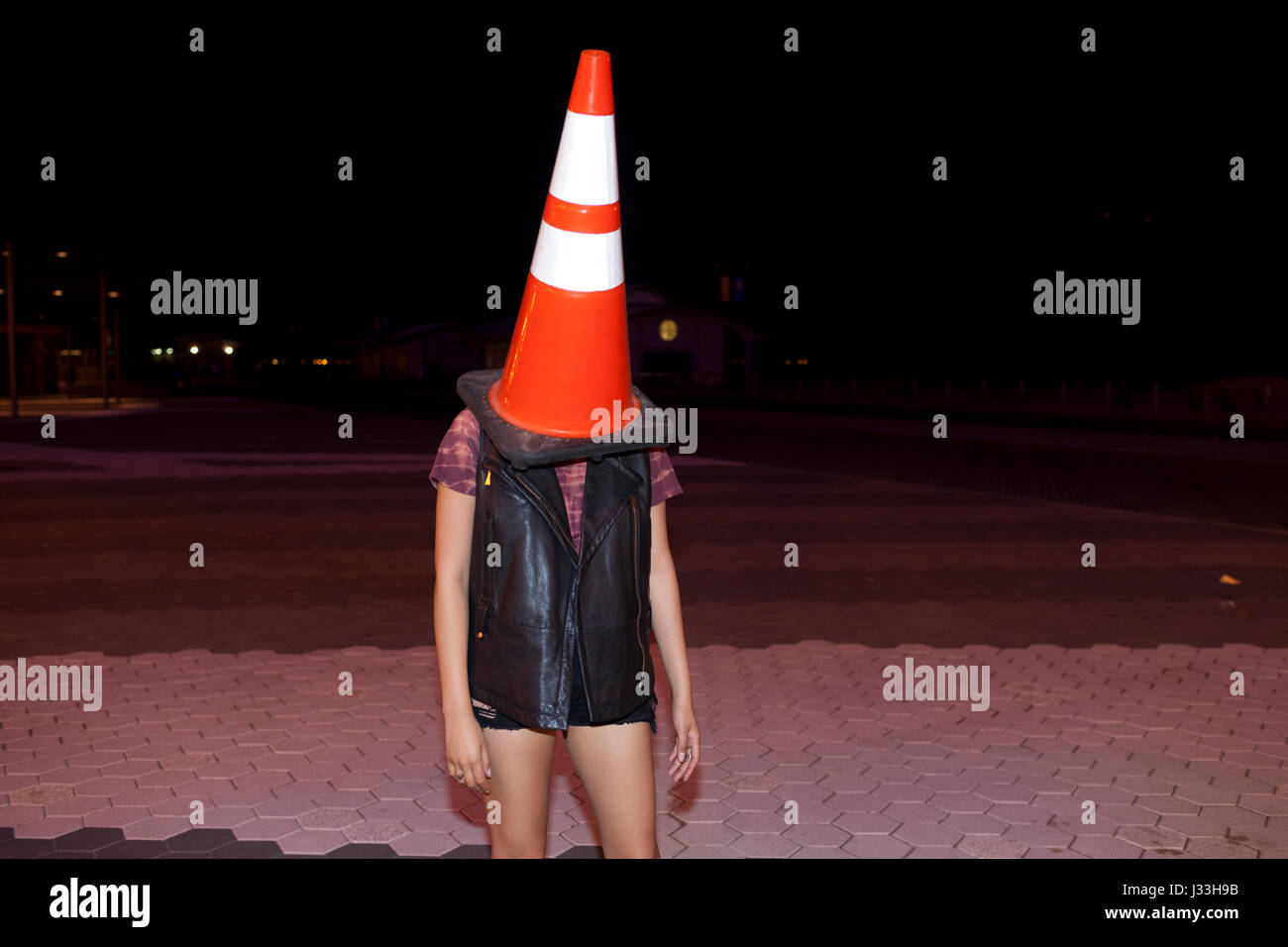 Playful young woman with a traffic cone on her head - Stock Image