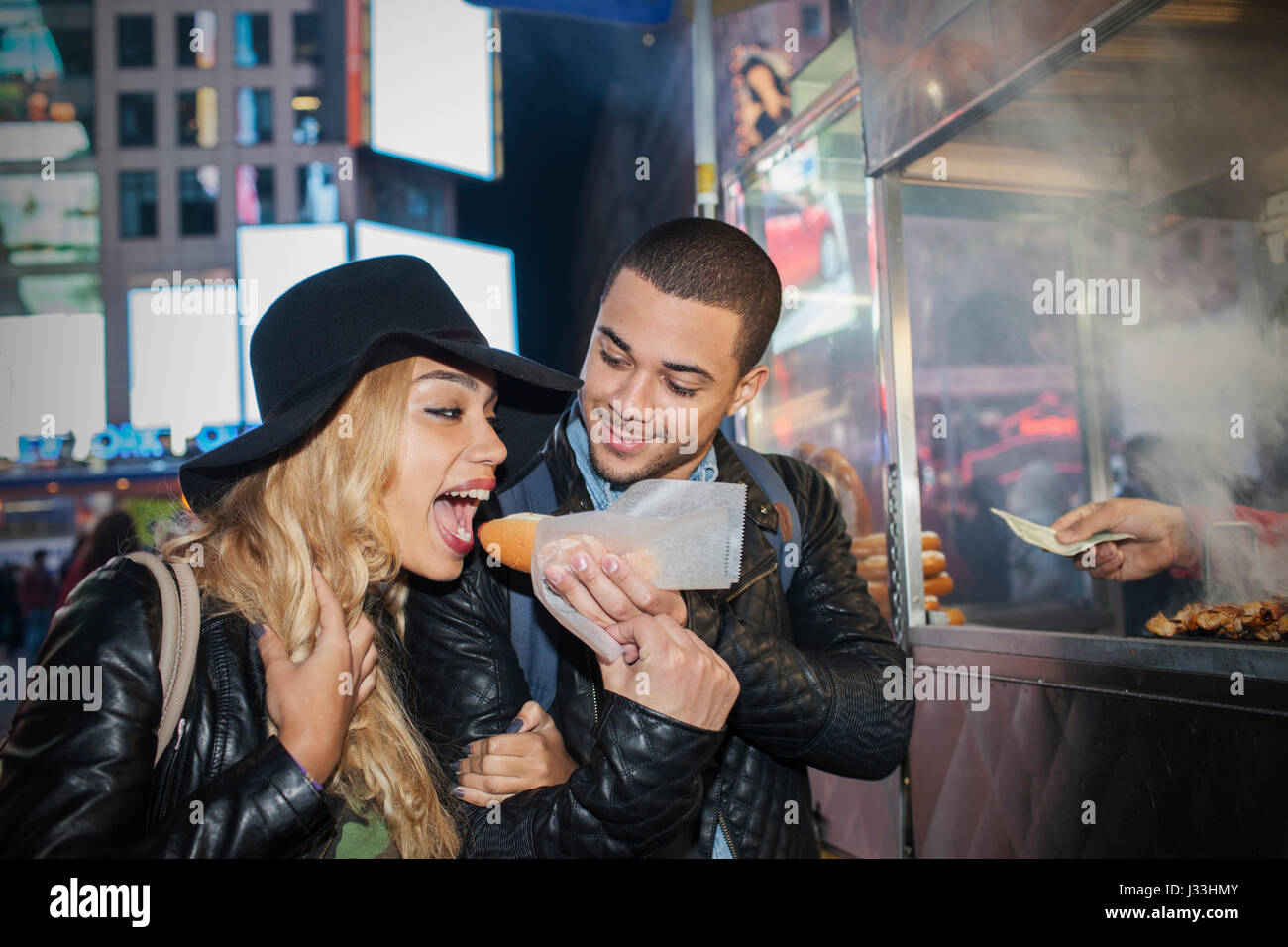 Young couple eating street food - Stock Image
