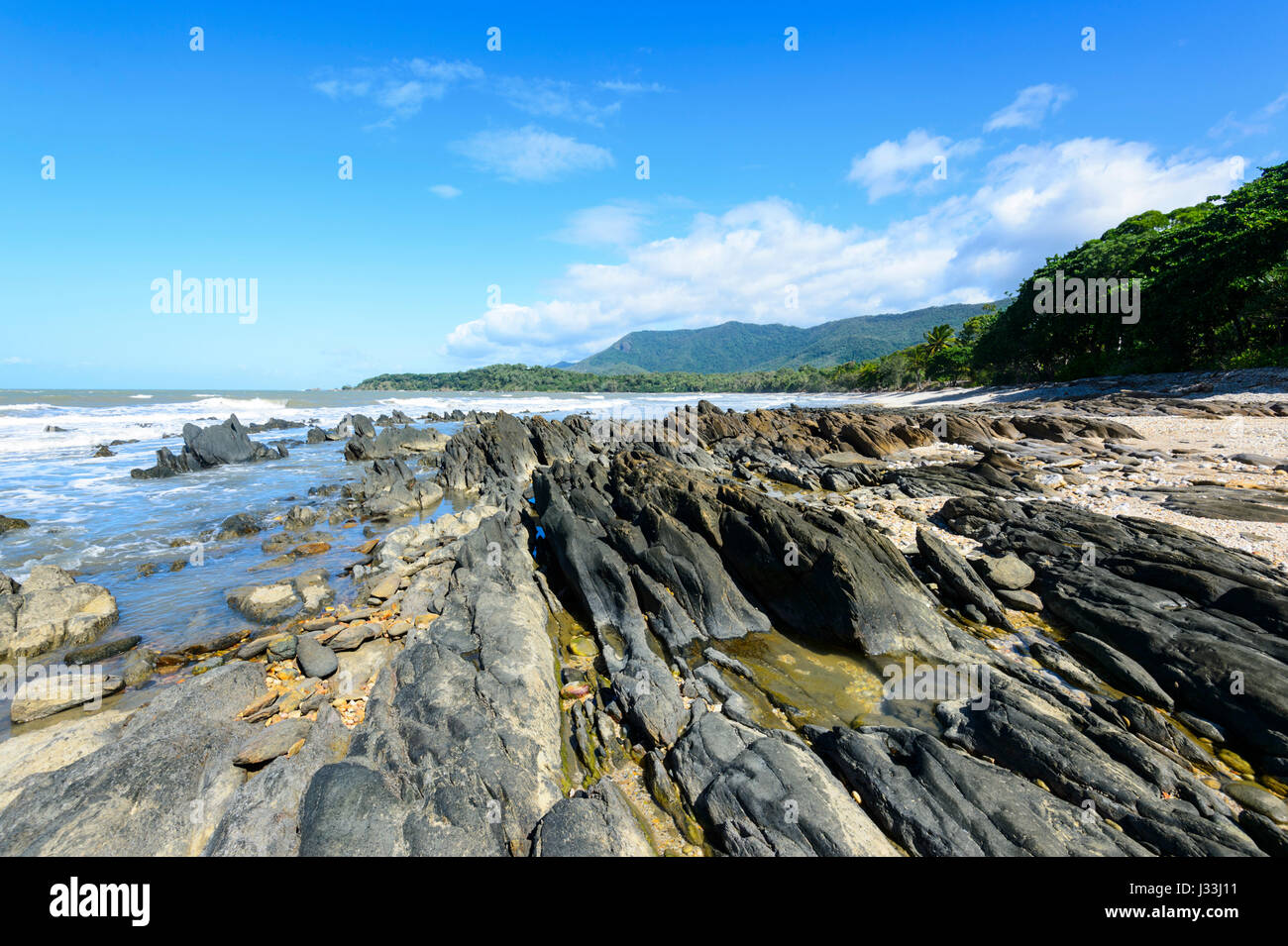 Scenic rugged rocky coast between Cairns and Port Douglas, Far North Queensland, FNQ, QLD, Australia - Stock Image