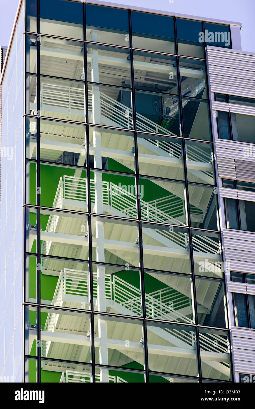 Metal Stairways with steps and railings of a multistory building, painted white, are viewed through a glass wall, - Stock Image