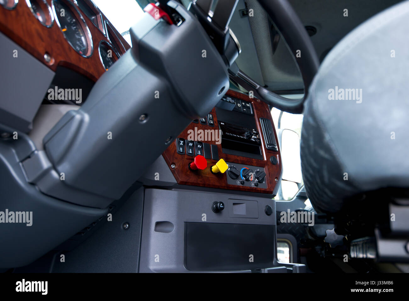 Modern ergonomic and stylish dashboard of heavy semi truck with lots of equipment, Steering column, indicators, - Stock Image