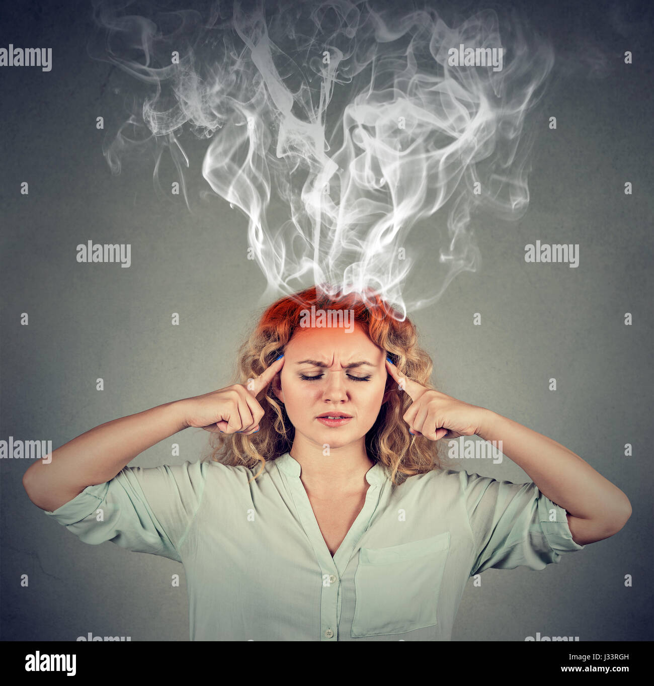 Woman thinks very intensely having headache isolated on gray wall background - Stock Image