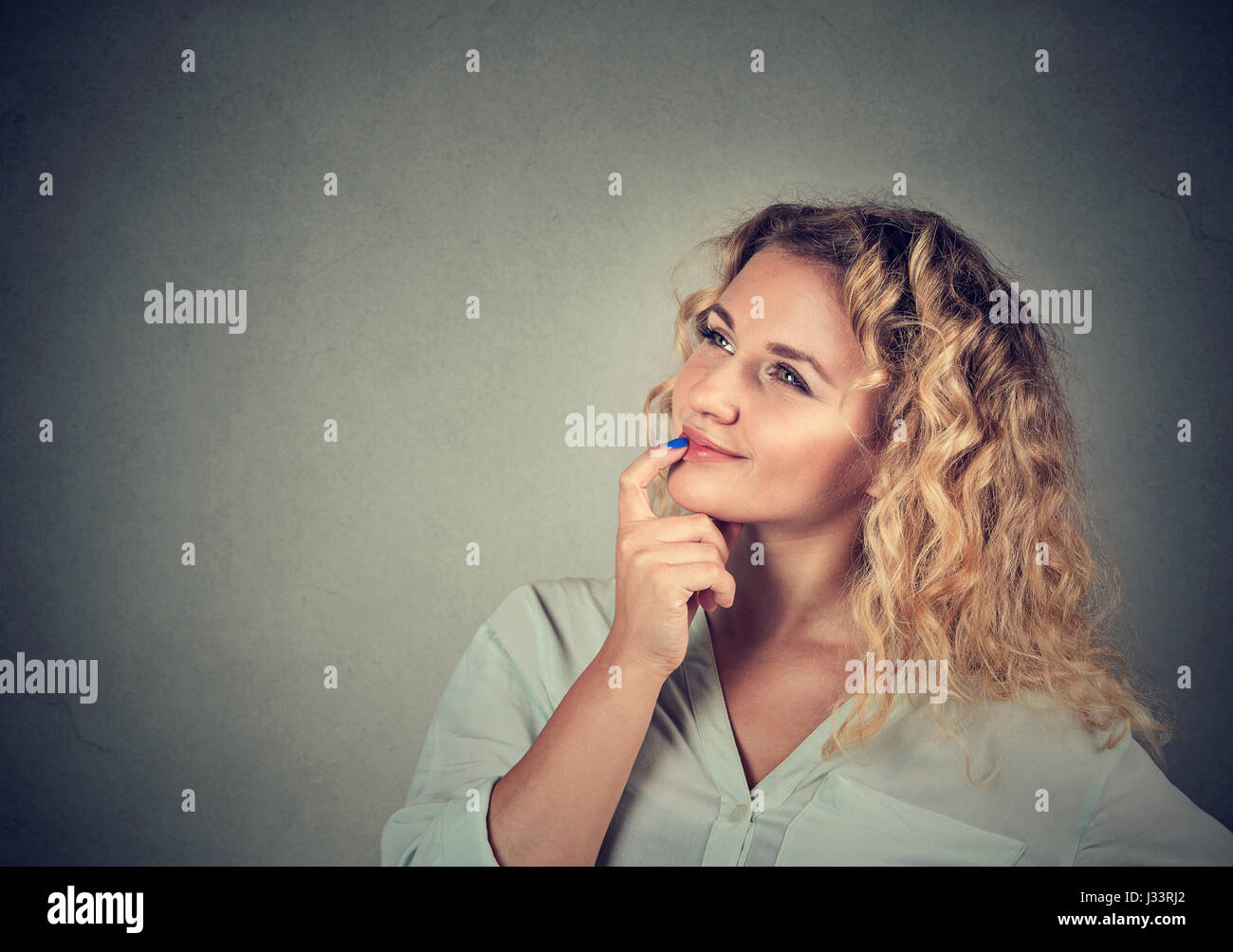 Portrait happy beautiful woman thinking looking up isolated on gray wall background with copy space. Human face Stock Photo