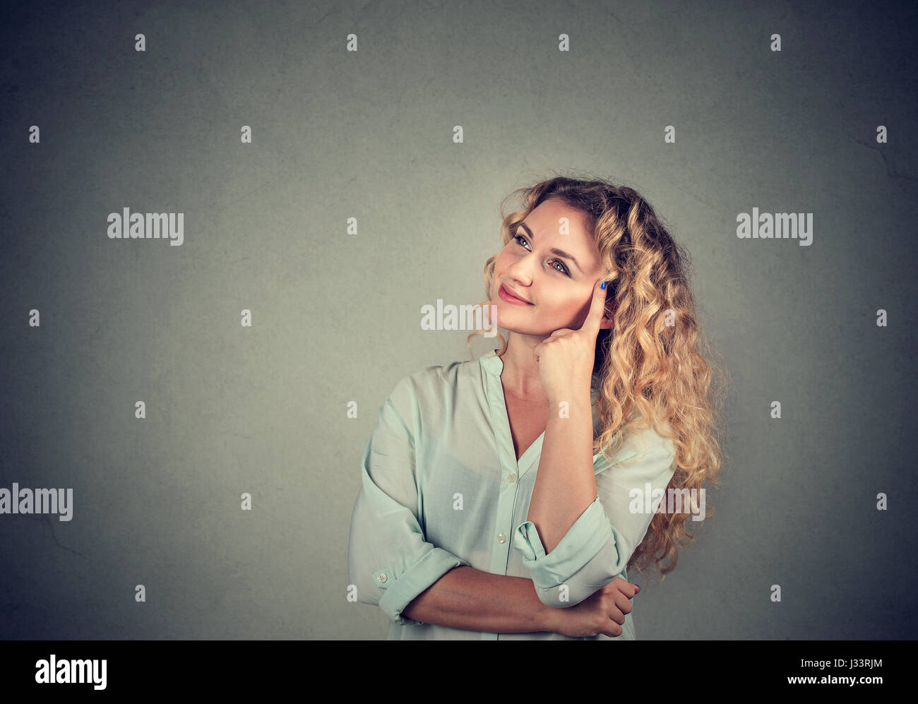 Portrait happy beautiful woman thinking looking up isolated on gray wall background with copy space. Human face - Stock Image