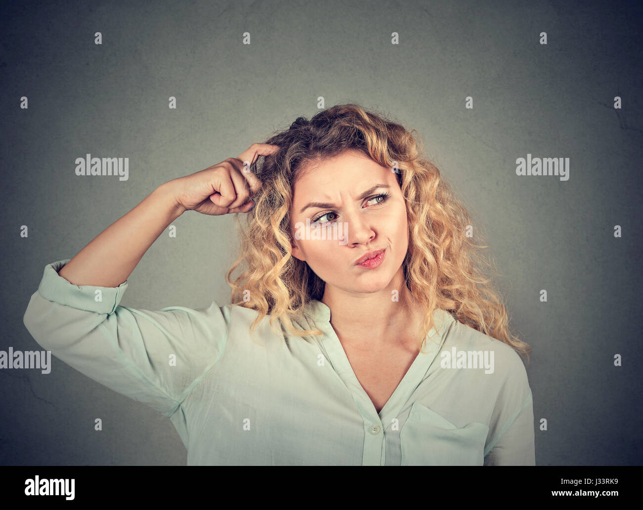 Young woman scratching head, thinking daydreaming about something looking up isolated on gray background. Human - Stock Image