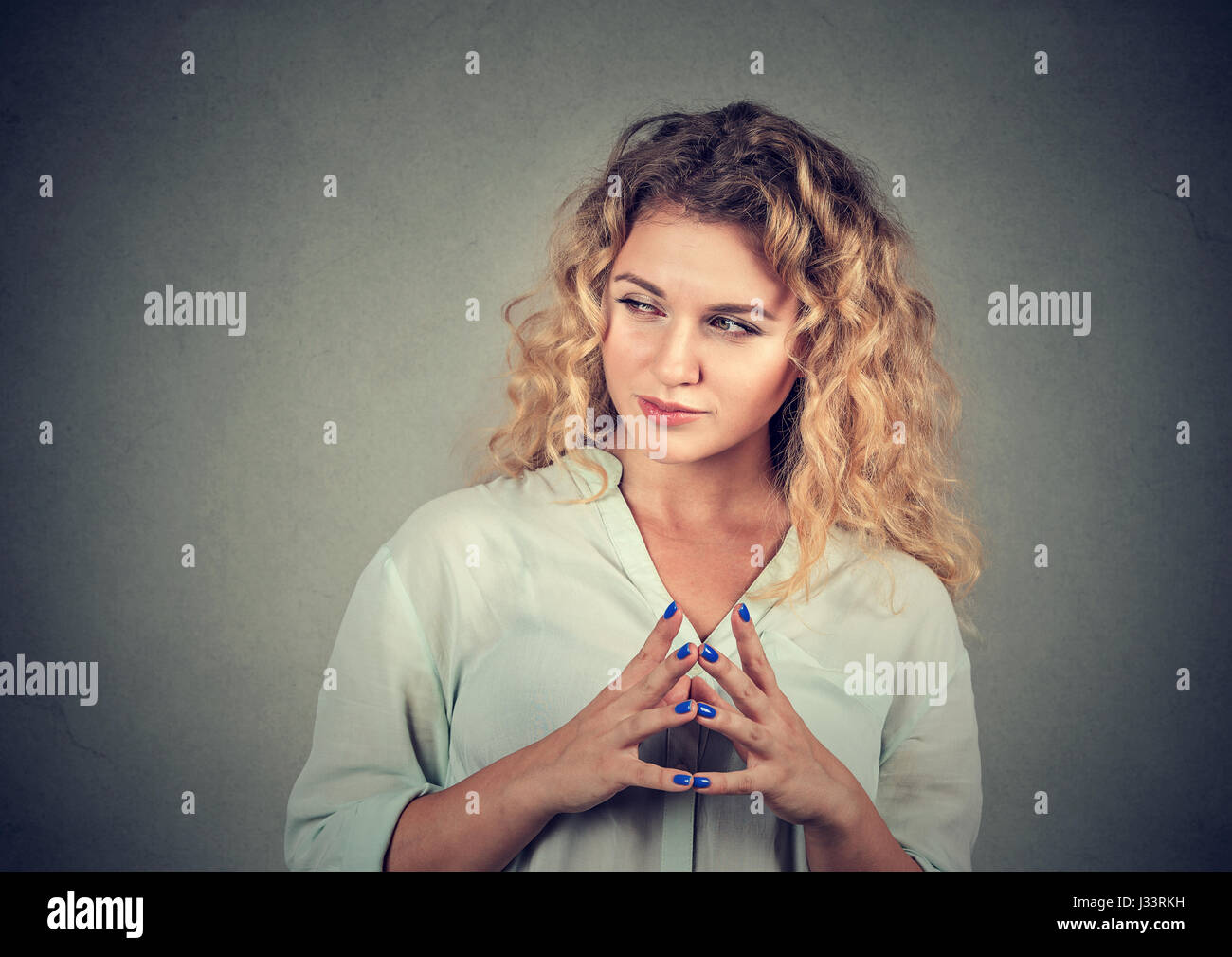 Closeup portrait of sneaky, sly, scheming young woman plotting something isolated on gray background. Negative human - Stock Image
