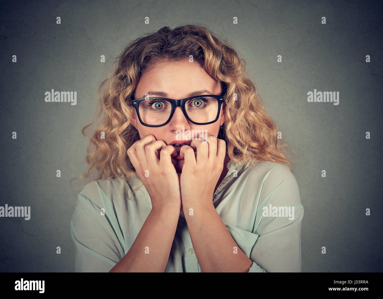 Closeup portrait nervous stressed young woman biting fingernails looking anxiously craving isolated gray background. - Stock Image