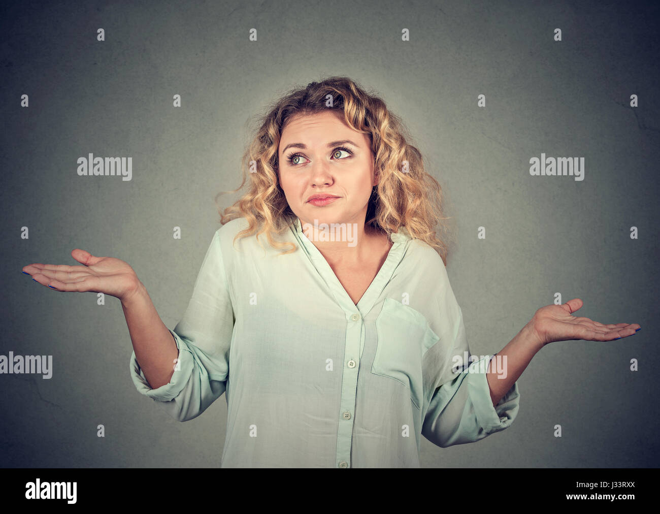 Portrait dumb looking woman arms out shrugs shoulders who cares so what I don't know isolated on gray wall background. - Stock Image