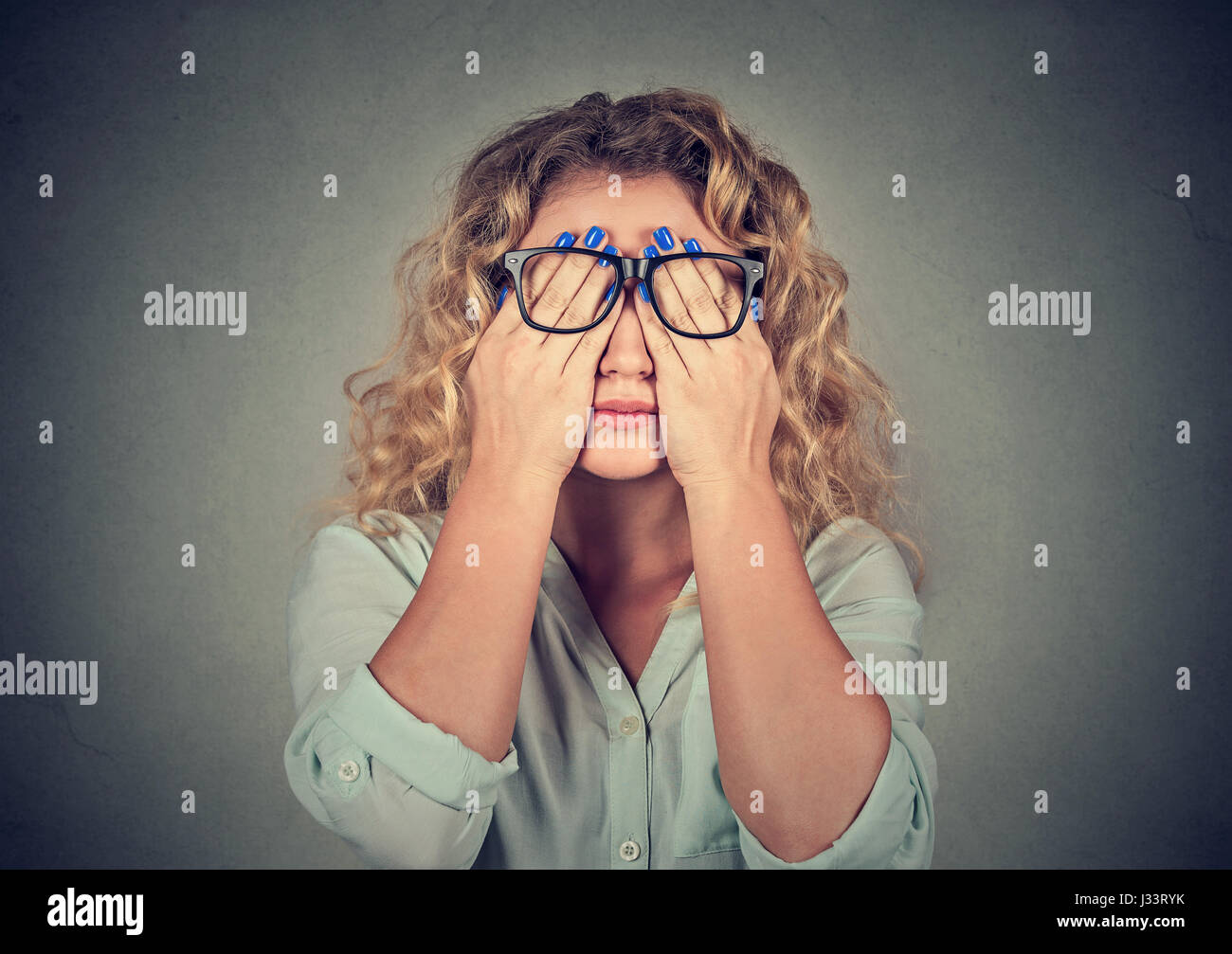 Closeup portrait young woman in glasses covering face eyes using her both hands isolated on gray wall background - Stock Image
