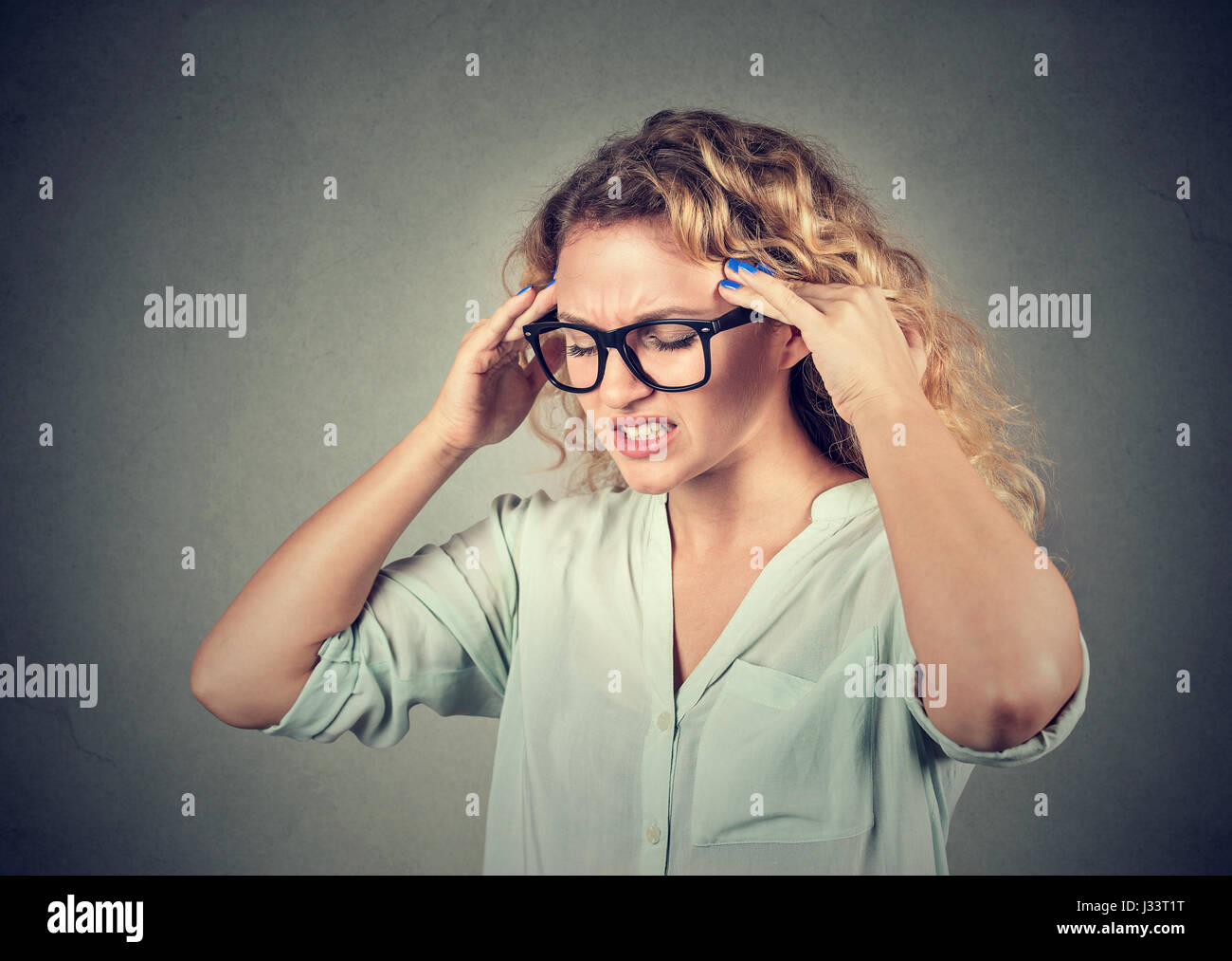 Closeup portrait sad young woman in glasses with worried stressed face expression isolated on gray wall background. - Stock Image