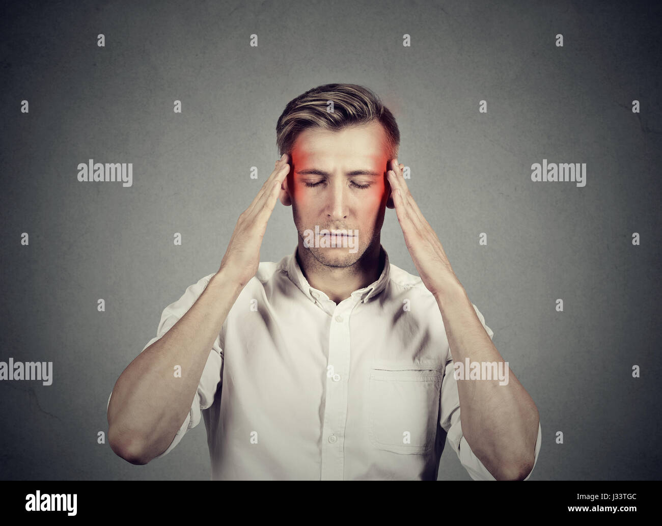 Man with headache thinking very intensely concentrating isolated on gray wall background - Stock Image