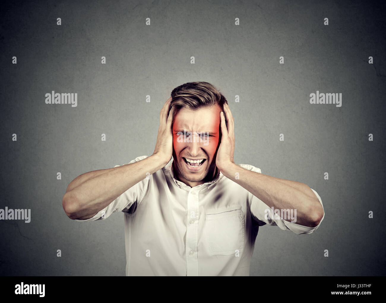 man with headache isolated on gray wall background - Stock Image