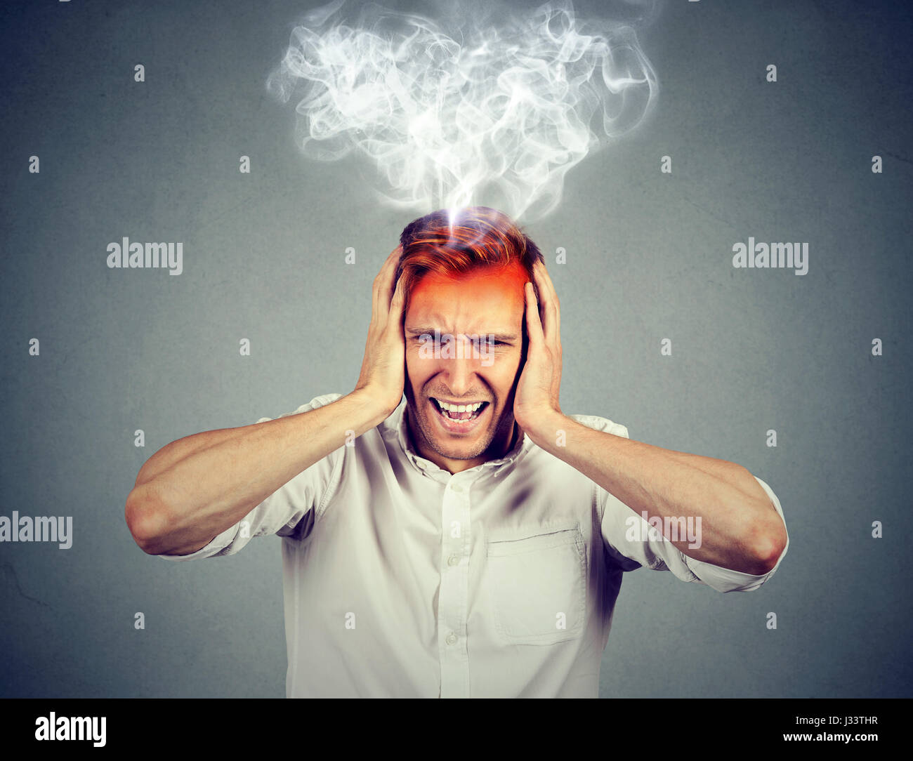 Portrait young stressed man screaming frustrated overwhelmed steam coming out up of head isolated on grey wall background. - Stock Image