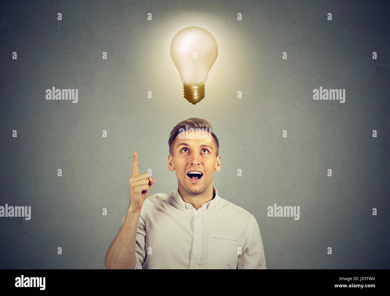 Young business man with idea solution and light bulb over his head - Stock Image
