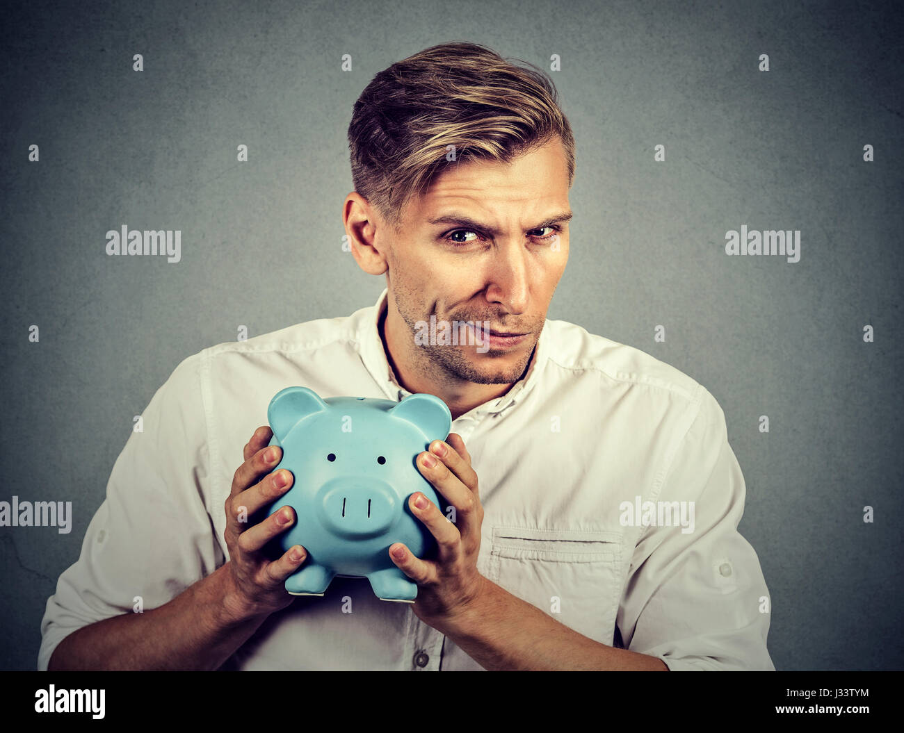 Young greedy stingy business man holding piggy bank isolated on gray wall background Stock Photo