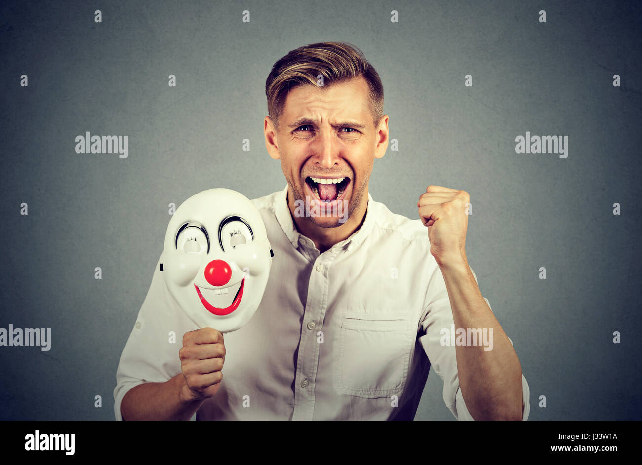 Portrait young upset angry screaming man holding a clown mask expressing cheerfulness happiness isolated on gray Stock Photo