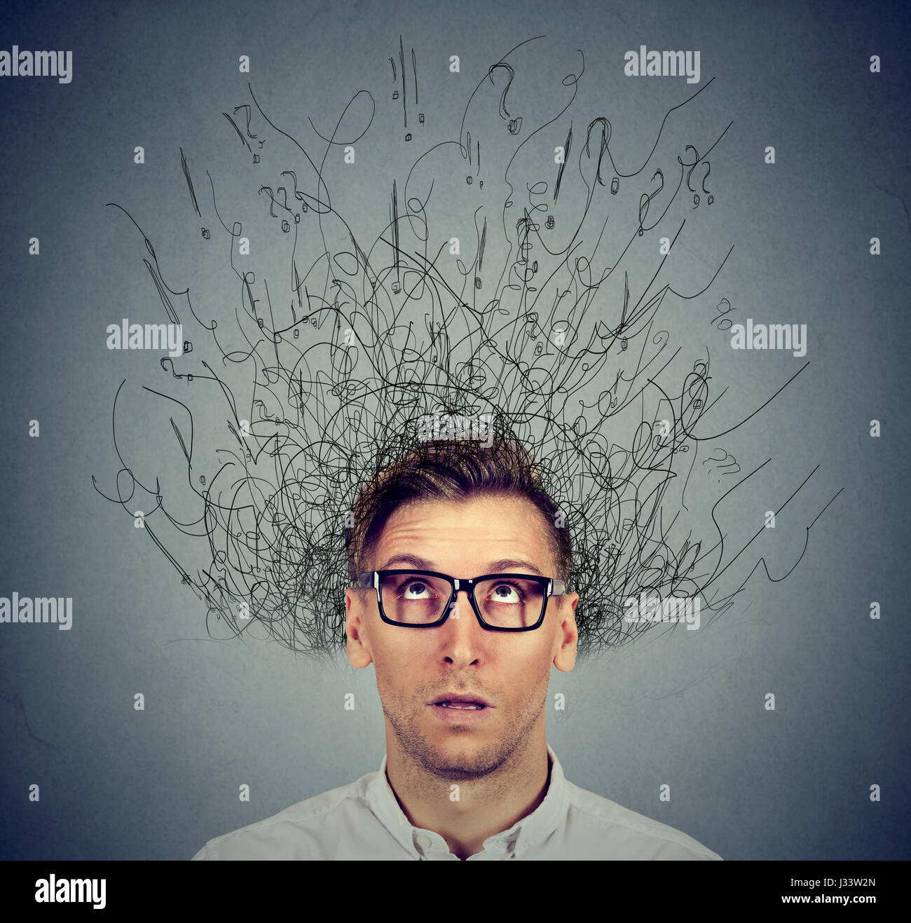 young man with worried stressed face expression and brain melting into lines question marks. Obsessive compulsive, - Stock Image