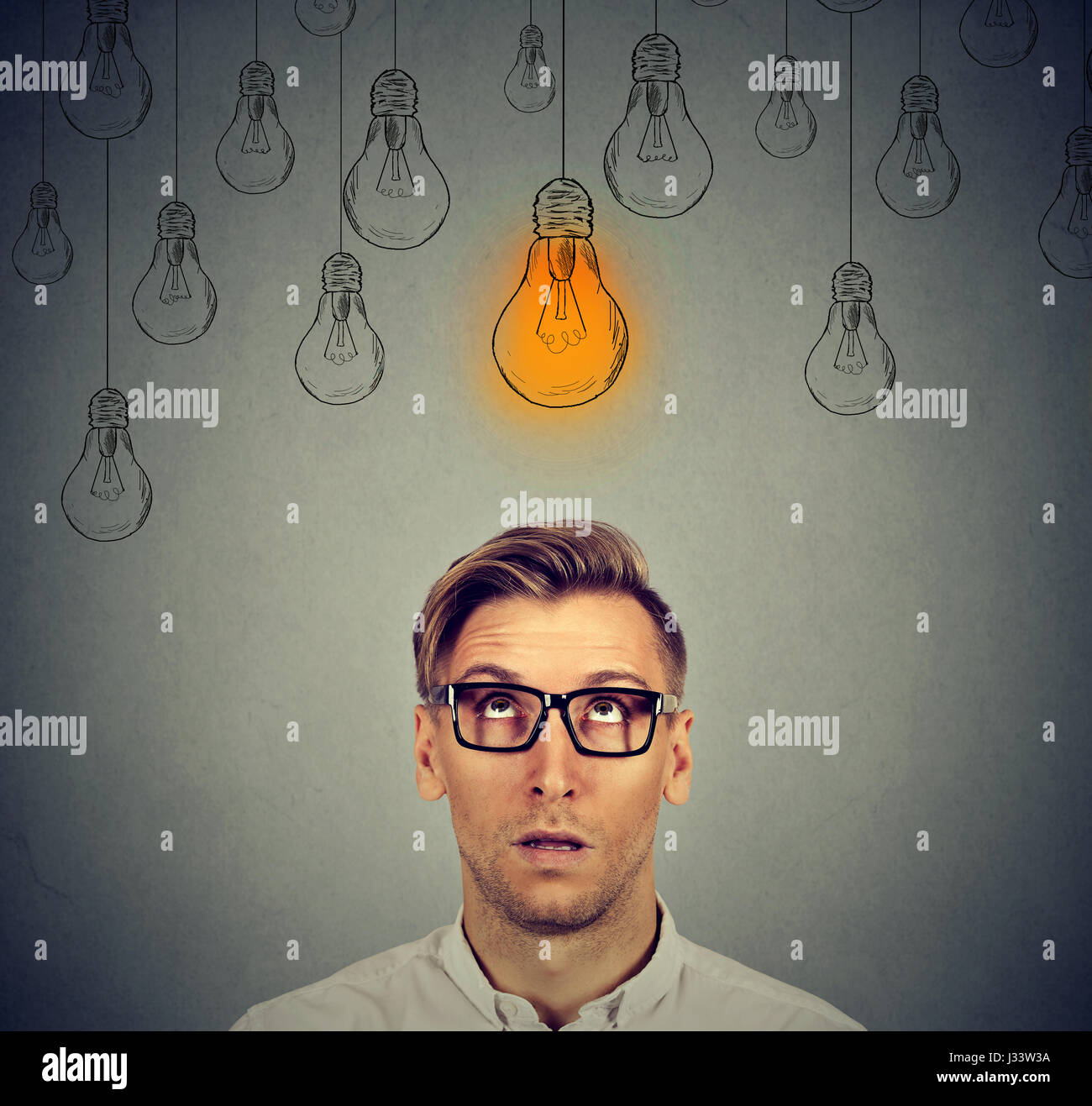 Thoughtful man in glasses looking up with light idea bulb sign above head has an idea isolated on gray wall background Stock Photo