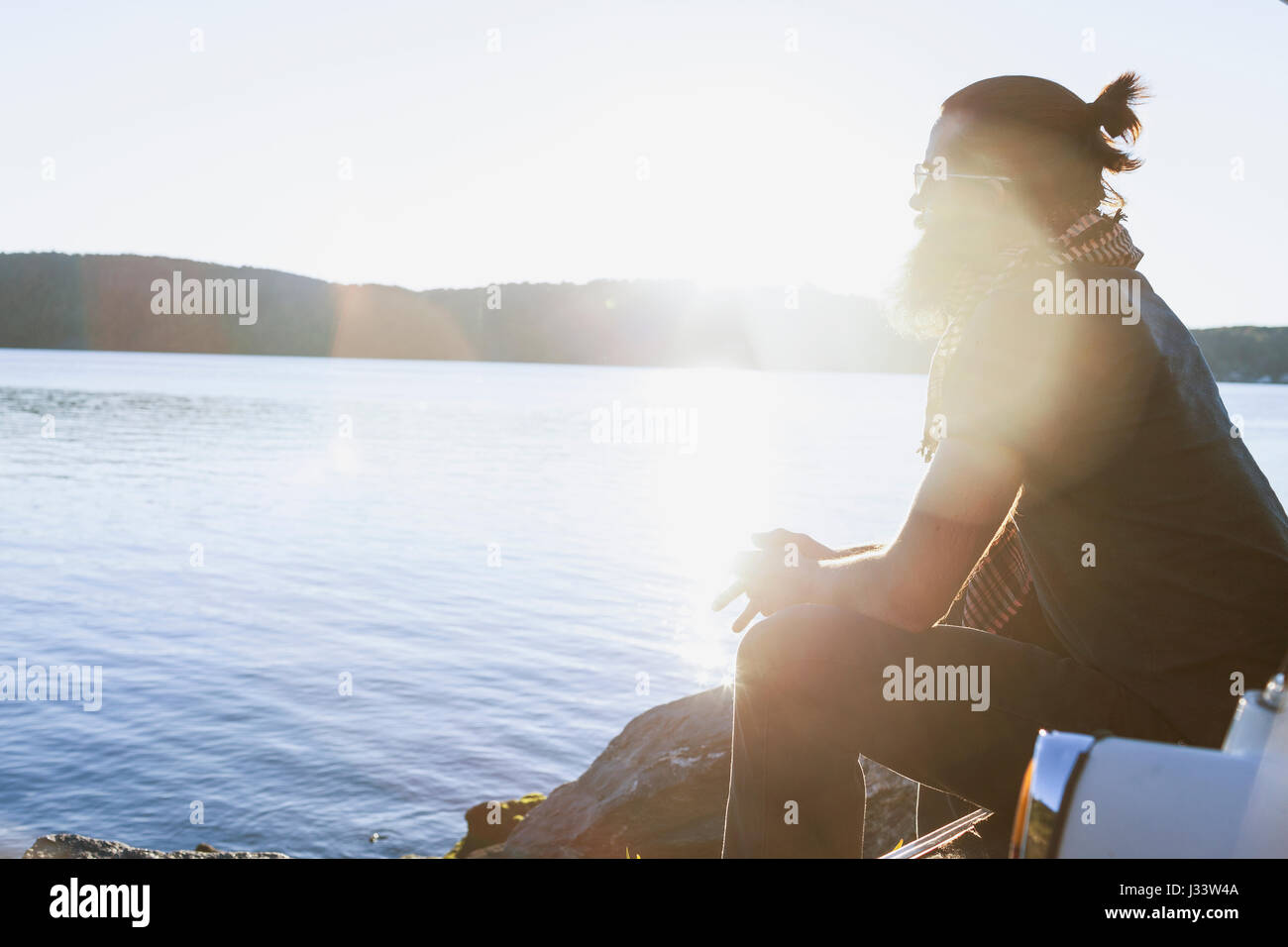 Young man admiring the view at a scenic lake - Stock Image