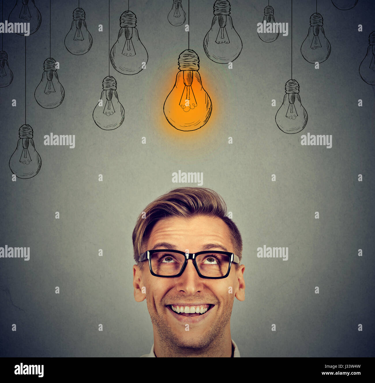 Portrait happy handsome man in glasses looking up at bright idea light bulb above head isolated on gray wall background - Stock Image