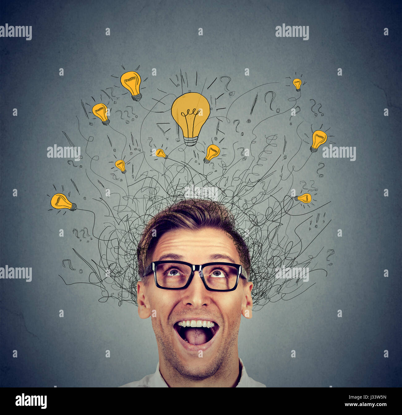 Happy man in glasses looking up with light idea bulb above head isolated on gray wall background - Stock Image