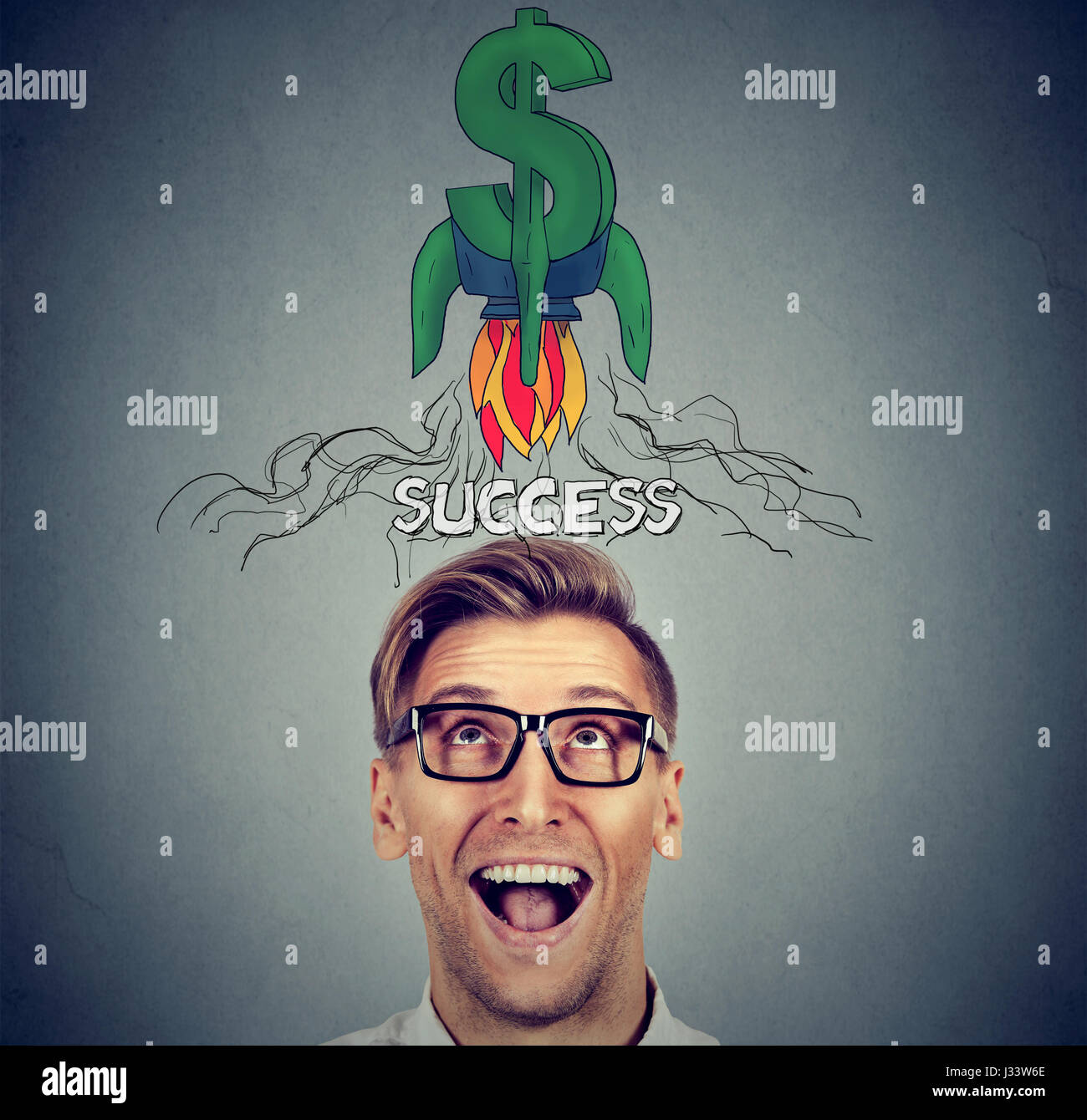 Financial business success concept. Surprised happy young man looking up - Stock Image