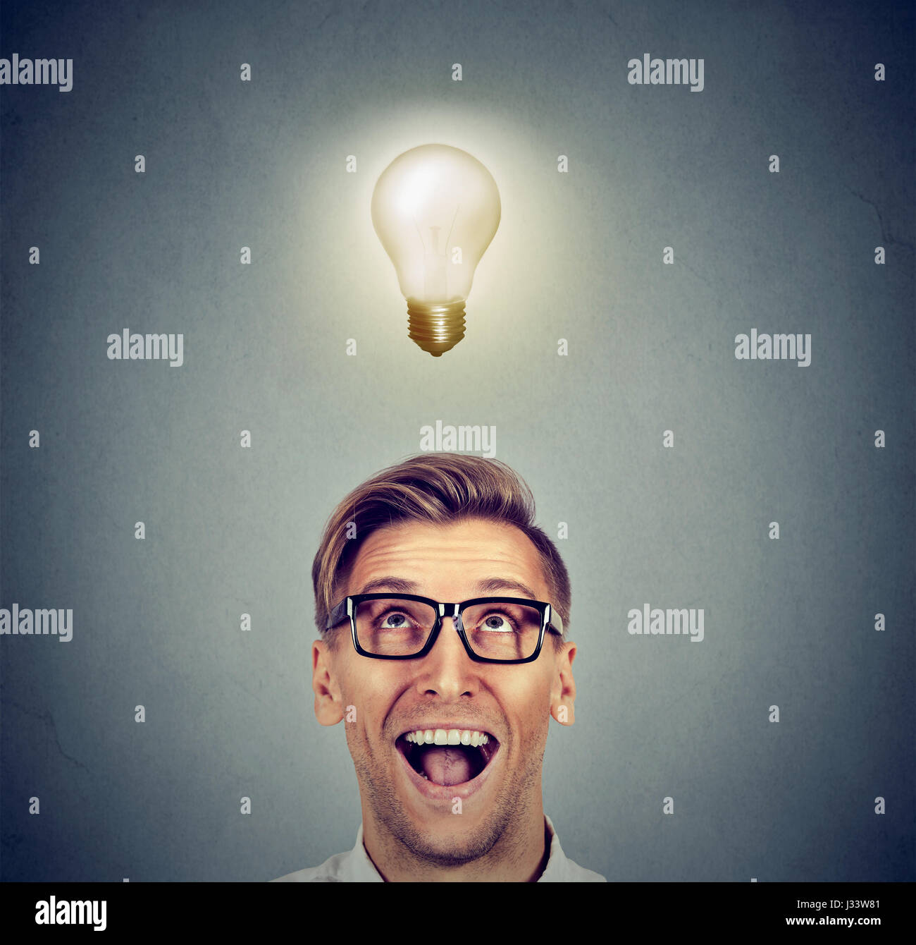 Happy man in glasses looking up at bright light idea bulb above head isolated on gray wall background - Stock Image