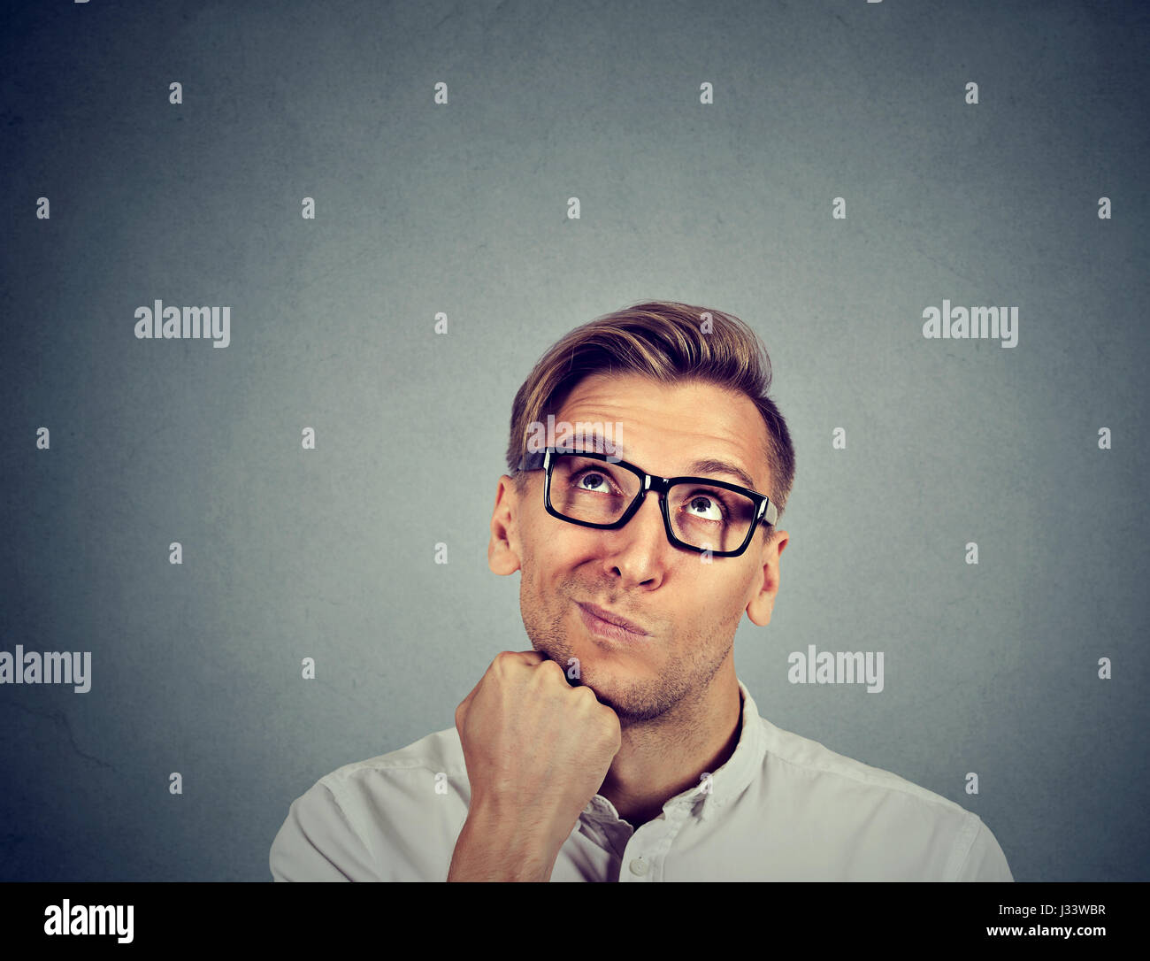 confused skeptical man thinking looking up isolated on gray background with copy space above head. Human face expressions, - Stock Image