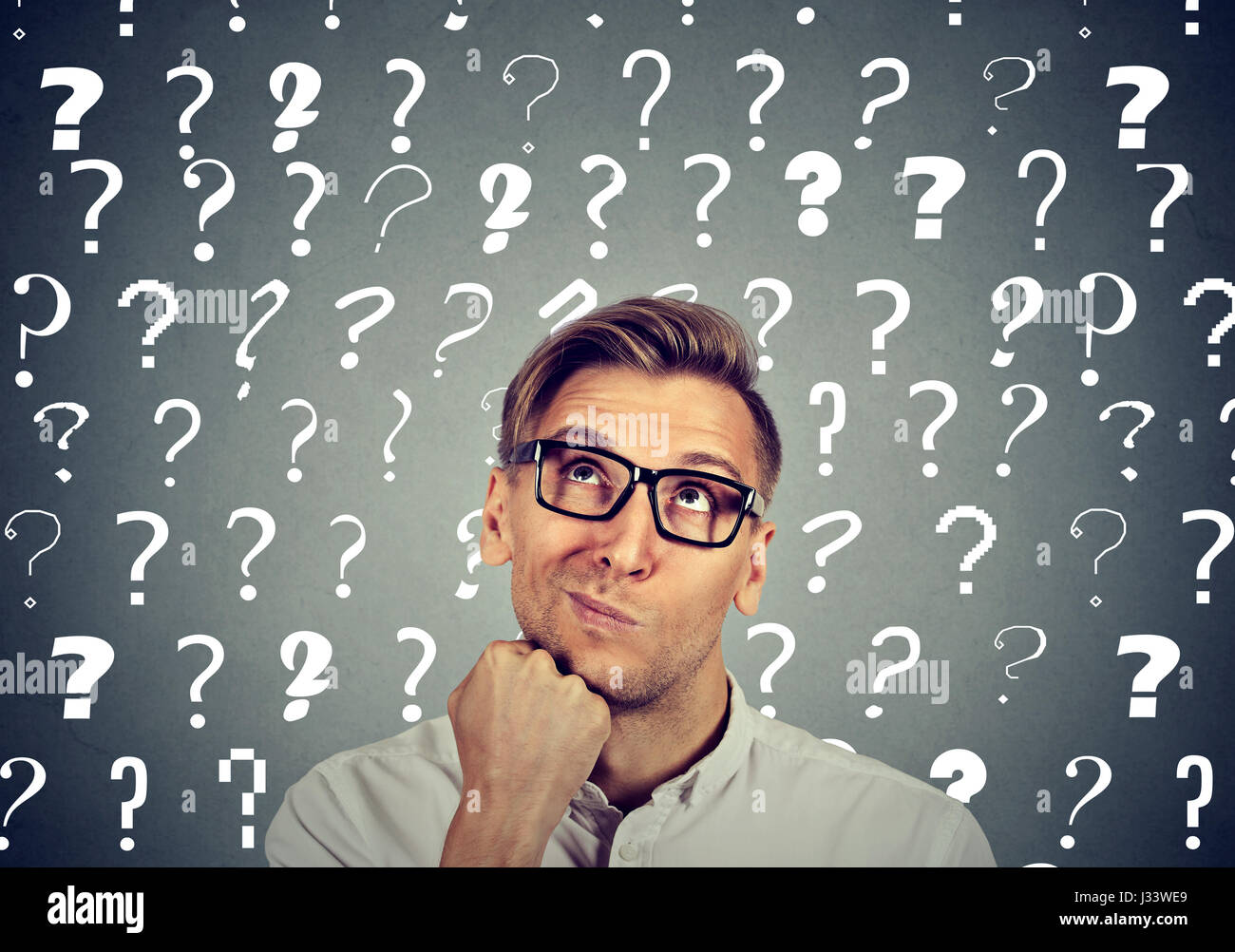 Thoughtful confused handsome man in glasses has too many questions and no answer - Stock Image