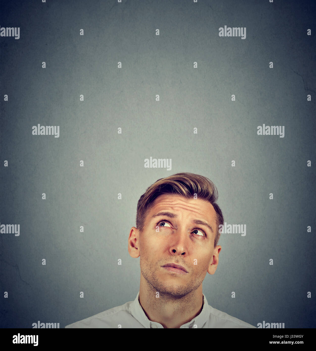 Headshot confused man thinking looking up isolated on gray wall background with copy space above head. Human face - Stock Image