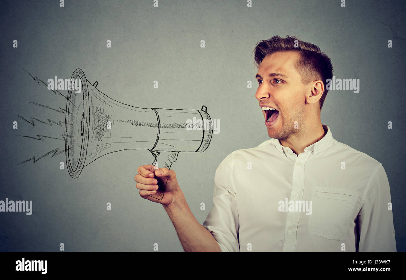 Portrait angry young man holding screaming in megaphone isolated on grey wall background. Negative face expression - Stock Image
