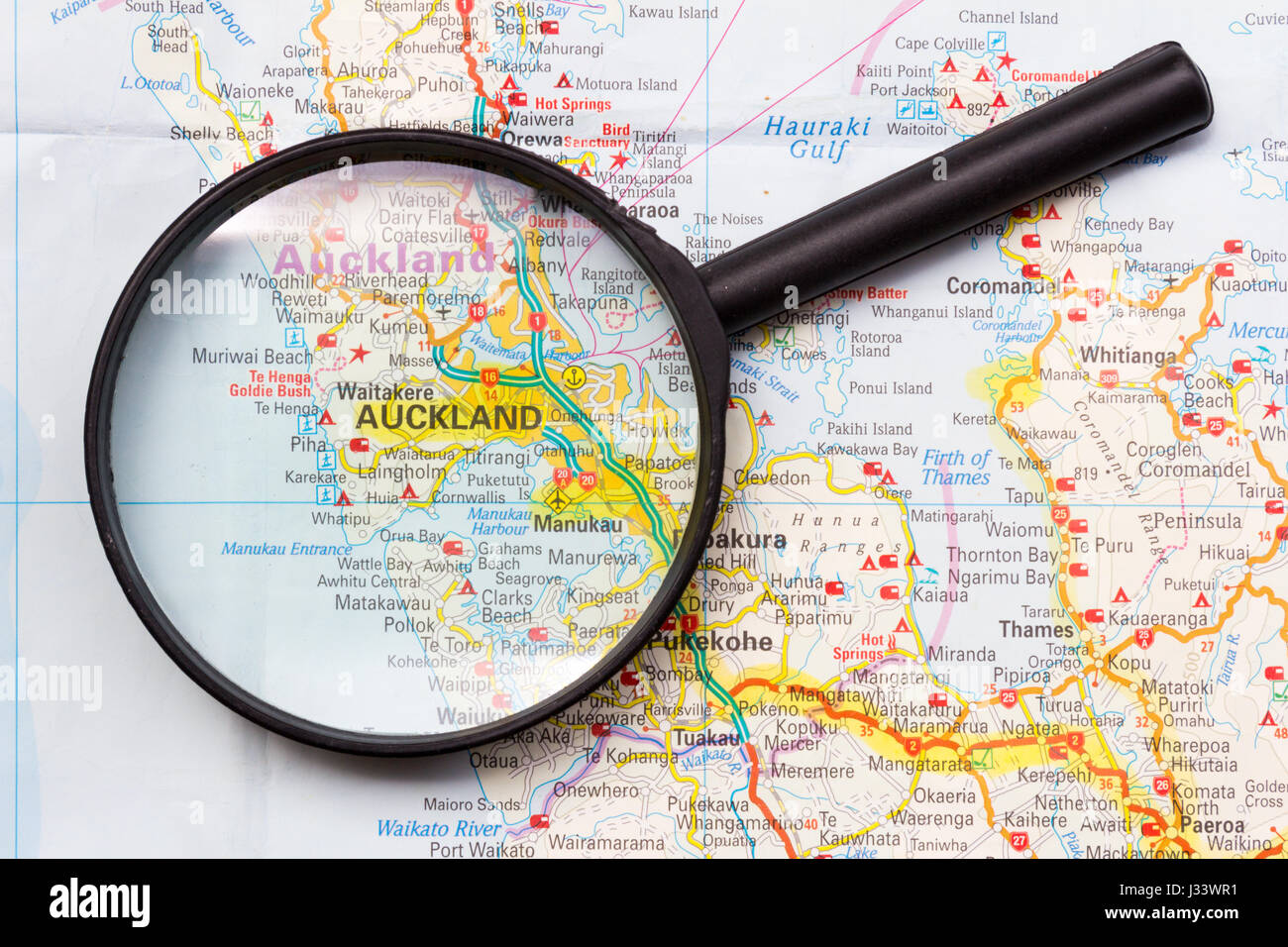 Map of New Zealand with magnifying glass focussing on Auckland, North Island - Stock Image