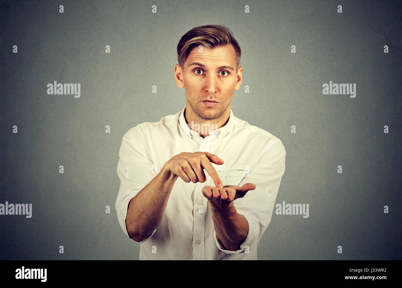 Young handsome man asking for more money to pay back debt - Stock Image
