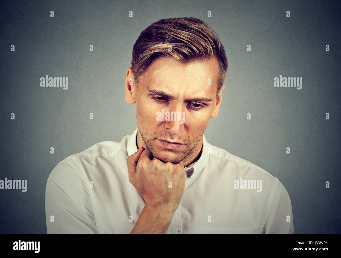 Closeup portrait sad young handsome man with worried stressed face expression looking down - Stock Image