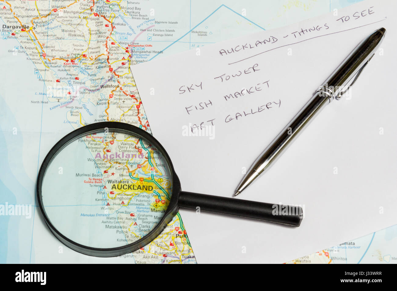 Map of New Zealand, list of things to see and with magnifying glass focussing on Auckland, North Island - Stock Image