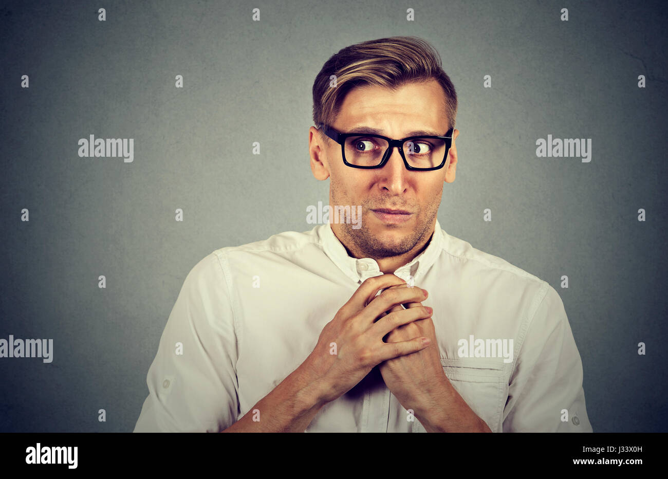 Nervous stressed young man student feels awkward looking away sideway anxiously craving something isolated gray - Stock Image