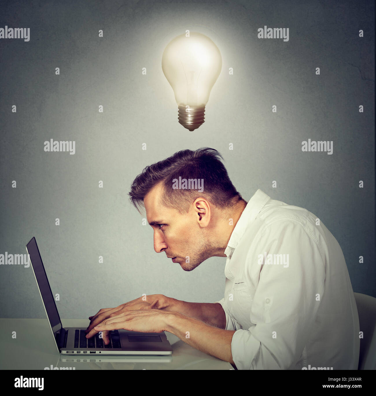 Side profile young man working on computer sitting at desk with light bulb over his head isolated on gray wall background. - Stock Image