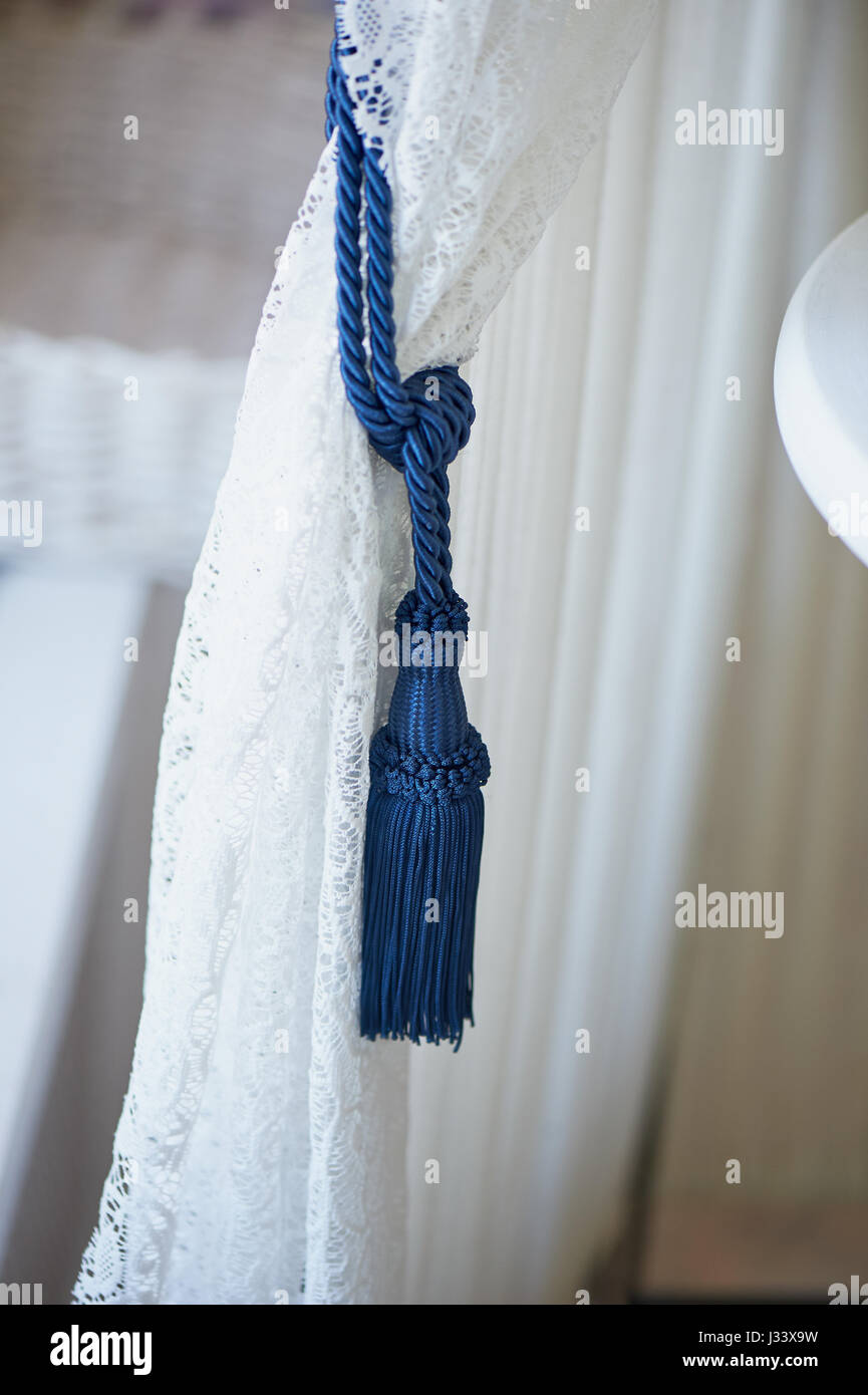 blue brush wings on a white lace curtain. The ease and tenderness - Stock Image